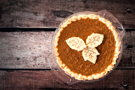 sweet table: Thanksgiving pumpkin pie with leaf pastry toppings against rustic wood background