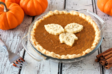 toppings: Autumn pumpkin pie with leaf pastry toppings against a rustic white wood background Stock Photo