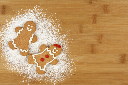 powdered sugar: Two Christmas gingerbread people with powdered sugar on wood background