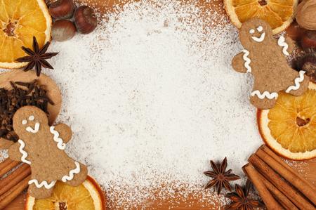 Vakantie bakken thema frame met peperkoek mannen noten en specerijen tegen een poedersuiker achtergrond