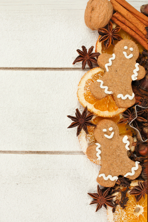 man nuts: Christmas baking side border with gingerbread men and holiday spices on white wood background