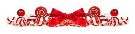 빨간색과 흰색 싸구려의 크리스마스 국경 활과 사탕 지팡이 흰 배경에 고립