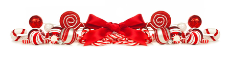 Christmas border of red and white baubles bows and candy canes isolated on a white background Stock Photo - 47675271