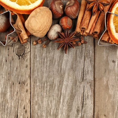 brown background: Top border of baking ingredients and holiday spices over a rustic wooden background
