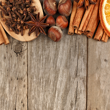rustic food: Top border of holiday spices and baking ingredients over a rustic wooden background