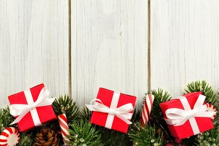 cajas navide�as: Navidad frontera inferior de regalos ramas y bastones de caramelo sobre un fondo de madera blanca