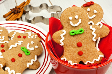 cute christmas: Christmas gingerbread man table scene with cookies in red bowl on white wood background