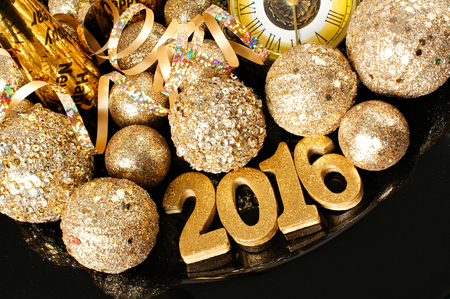 new years eve party: New Years Eve 2016 golden numbers surrounded by shiny decorations Stock Photo