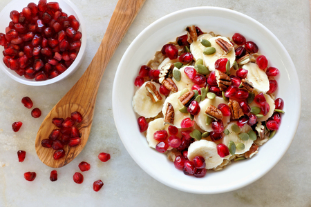 Healthy breakfast oatmeal with pomegranate bananas seeds and nuts overhead scene on white marble Stock Photo