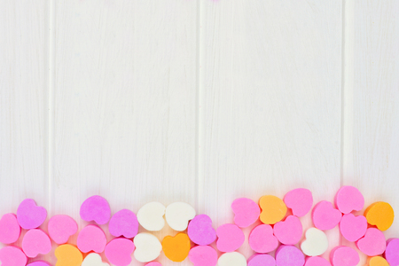 valentines day: Valentines Day sugar candy hearts forming a bottom border over a white wood background
