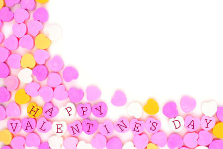 candy border: Pastel colored candy hearts with Happy Valentines Day text forming a corner border over white