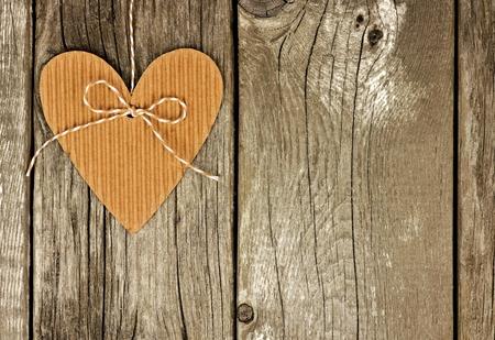 madera rústica: Rústica en forma de corazón etiqueta de regalo de cartón que cuelga sobre un fondo de madera de época