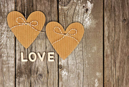 valentine card: Rustic heart shaped gift tags with LOVE wood letters hanging against a vintage wooden background