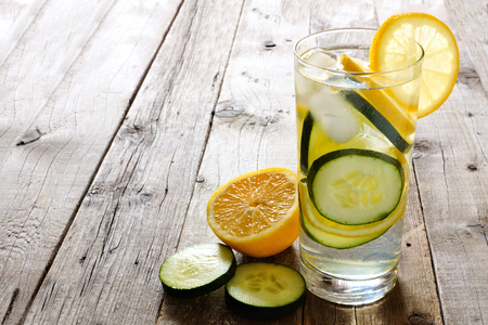 소박한 나무 배경에 대해 슬라이스 유리에 레몬 오이 해독 물