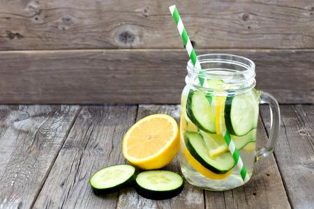 소박한 나무 배경에 대해 짚과 슬라이스 메이슨 항아리 잔에 레몬 오이 해독 물