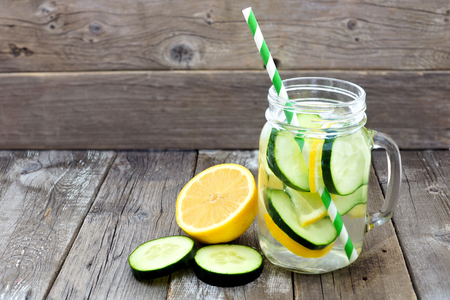 Lemon cucumber detox water in a mason jar glass with straw and slices against a rustic wood background Reklamní fotografie