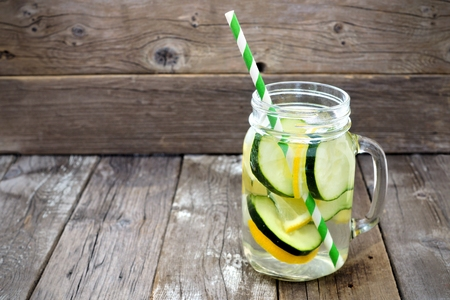 of straw: Lemon cucumber detox water in a mason jar glass with straw against a rustic wood background