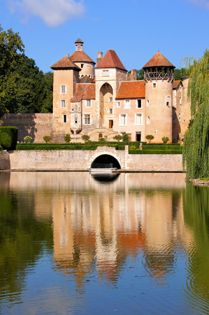 Medieval lakeside chateau with reflections in the Burgundy region of France Redactioneel