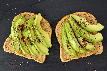 dark grey slate: Open avocado sandwiches with chia seeds on whole grain bread against a dark slate background