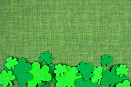 cloverleaf: St Patricks Day bottom border of shamrock confetti over a green linen background