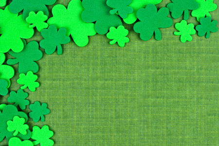 St Patricks Day corner border of shamrock confetti over a green linen background Stock Photo