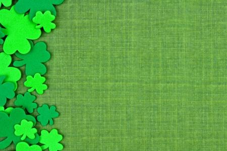 녹색 린 넨 배경 위에 토끼풀 색종이의 세인트 Patricks 주 측면 테두리