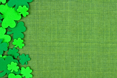 St Patricks Day side border of shamrock confetti over a green linen background Stok Fotoğraf