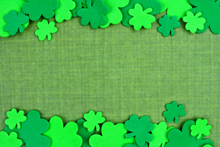 cloverleaf: St Patricks Day double border of shamrock confetti over a green linen background Stock Photo