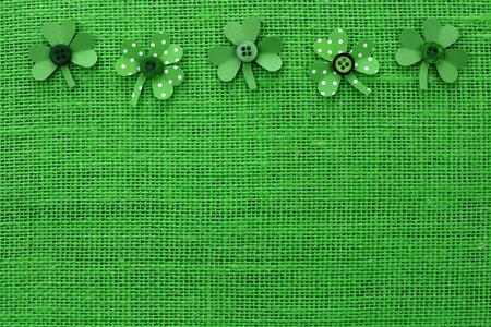 cloverleaf: St Patricks Day top border of handmade paper shamrocks over a green burlap background