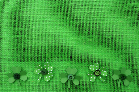 cloverleaf: St Patricks Day bottom border of handmade paper shamrocks over a green burlap background Stock Photo