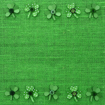 paddys: St Patricks Day double border of handmade paper shamrocks over a green burlap background