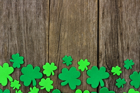cloverleaf: St Patricks Day bottom border of shamrocks over a rustic wooden background Stock Photo