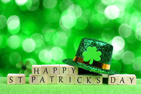 Happy St Patricks Day wooden blocks with leprechaun hat and shamrock over twinkling green background