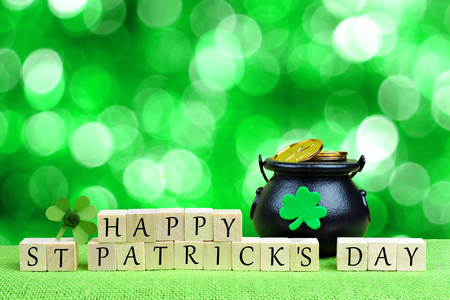 Happy St Patricks Day wooden blocks with Pot of Gold and shamrock over twinkling green background Stock Photo