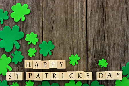 Happy St Patricks Day wooden blocks with corner border of shamrocks over a rustic wooden background