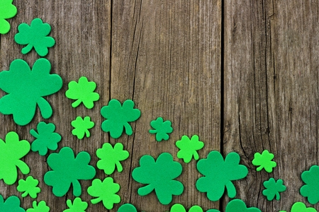 cloverleaf: St Patricks Day bottom corner border of shamrocks over a rustic wooden background