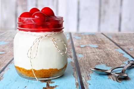 cereza: pastel de queso de la cereza dulce en un frasco de vidrio sobre un fondo de madera r�stica