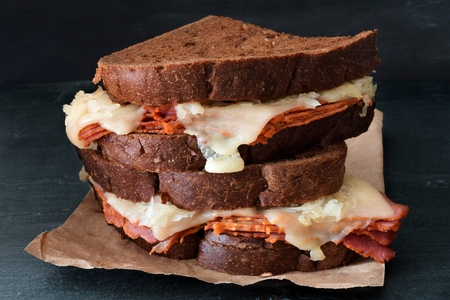 reuben: Stacked Reuben Sandwiches with corned beef and melted Swiss cheese against a dark slate background Stock Photo