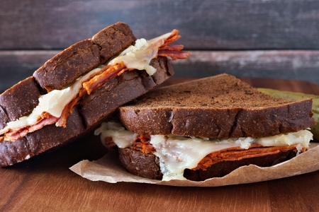 reuben: Reuben sandwiches stacked with corned beef and melted Swiss cheese with rustic wood background