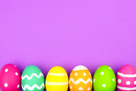 blue background: Colorful Easter egg bottom border over a soft purple paper background