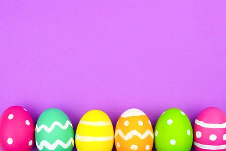 blue green background: Colorful Easter egg bottom border over a soft purple paper background