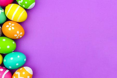 부드러운 보라색 종이 배경 위에 다채로운 부활절 달걀 측 경계 스톡 콘텐츠