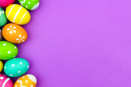 Colorful Easter egg side border over a soft purple paper background Stockfoto