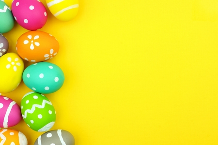 Colorful Easter egg side border over a yellow paper background