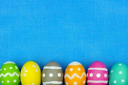 Colorful Easter egg bottom border over a blue burlap background