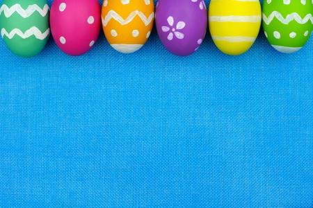la parte superior del huevo Pascua borde de colores sobre un fondo de arpillera azul Foto de archivo