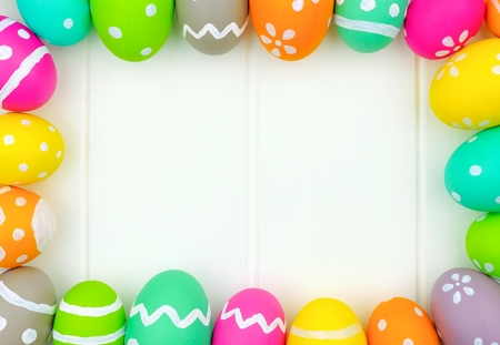 blue background: Colorful Easter egg frame around a white wood background Stock Photo