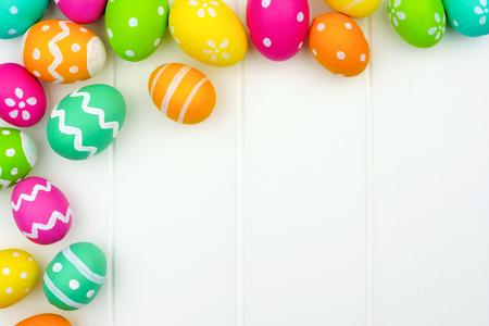 huevo: Colorido Pascua frontera de la esquina de huevo sobre un fondo de madera blanca