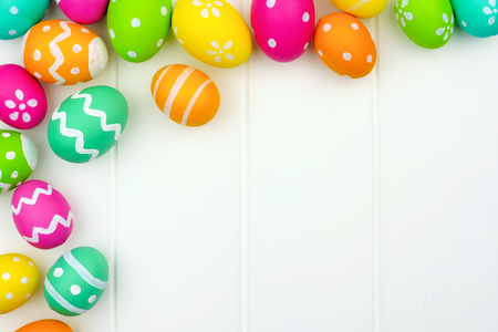 huevos de pascua: Colorido Pascua frontera de la esquina de huevo sobre un fondo de madera blanca