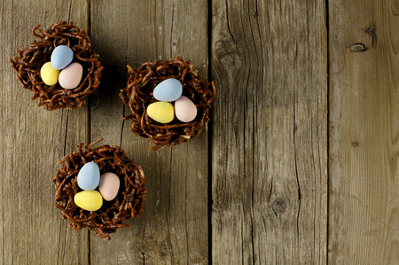nest: Springtime chocolate nests filled with candy eggs on a rustic wood background Stock Photo